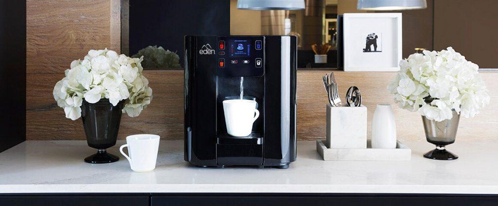 dispensador de agua pura pure negro en cocina con taza blanca