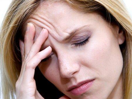 mujer con dolor de cabeza por falta de agua e hidratación