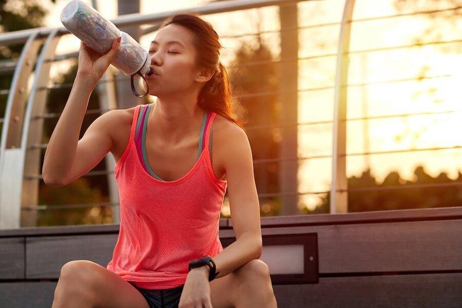 mujer sentada despues del ejercicio para hidratarse bien con agua purificada